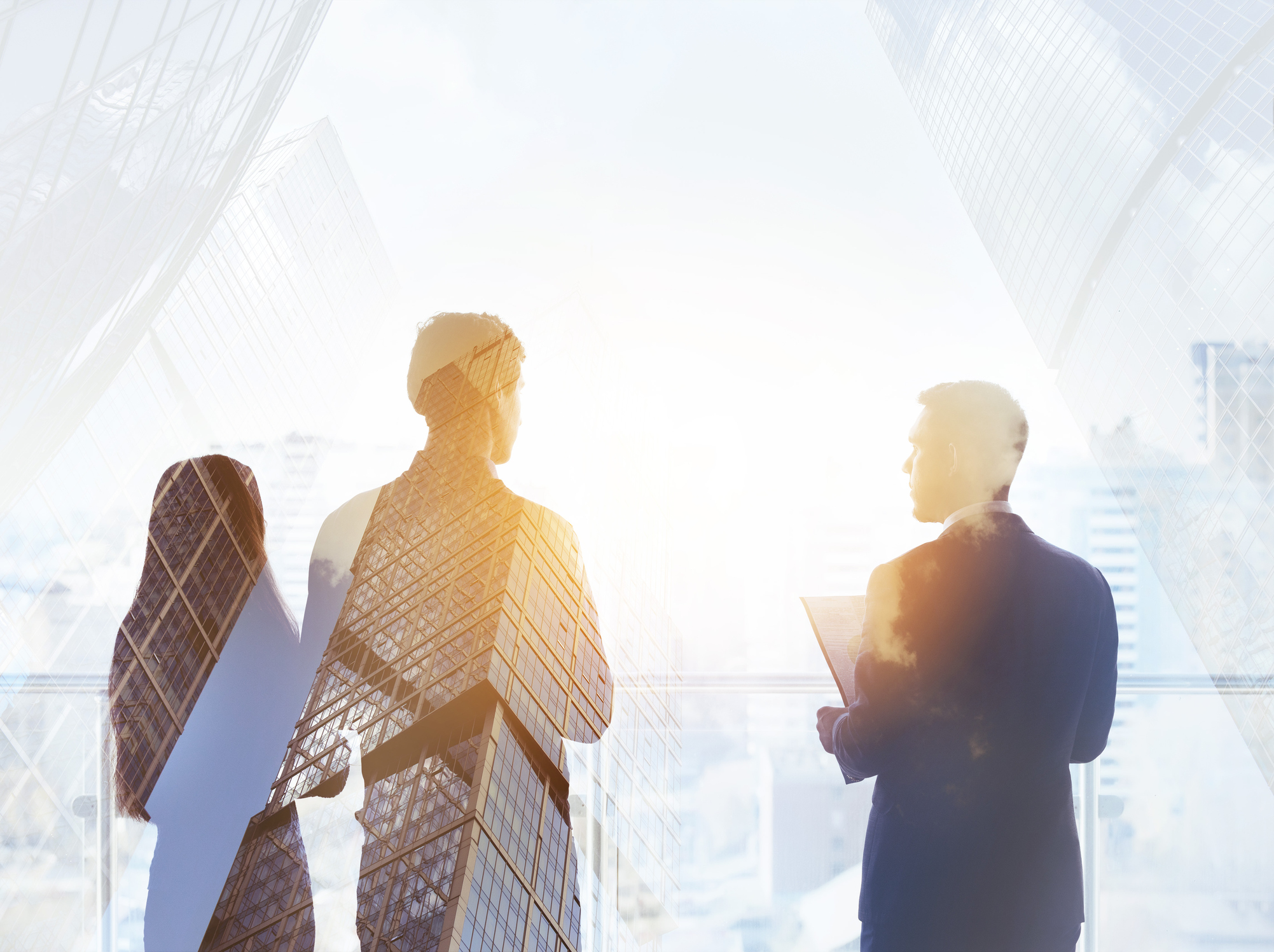 Abstract business concept with three silhouettes of businessmen double exposed on modern skyscrapers backdrop.